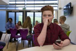 Teenage White Boy holding cellphone at cafeteria table
