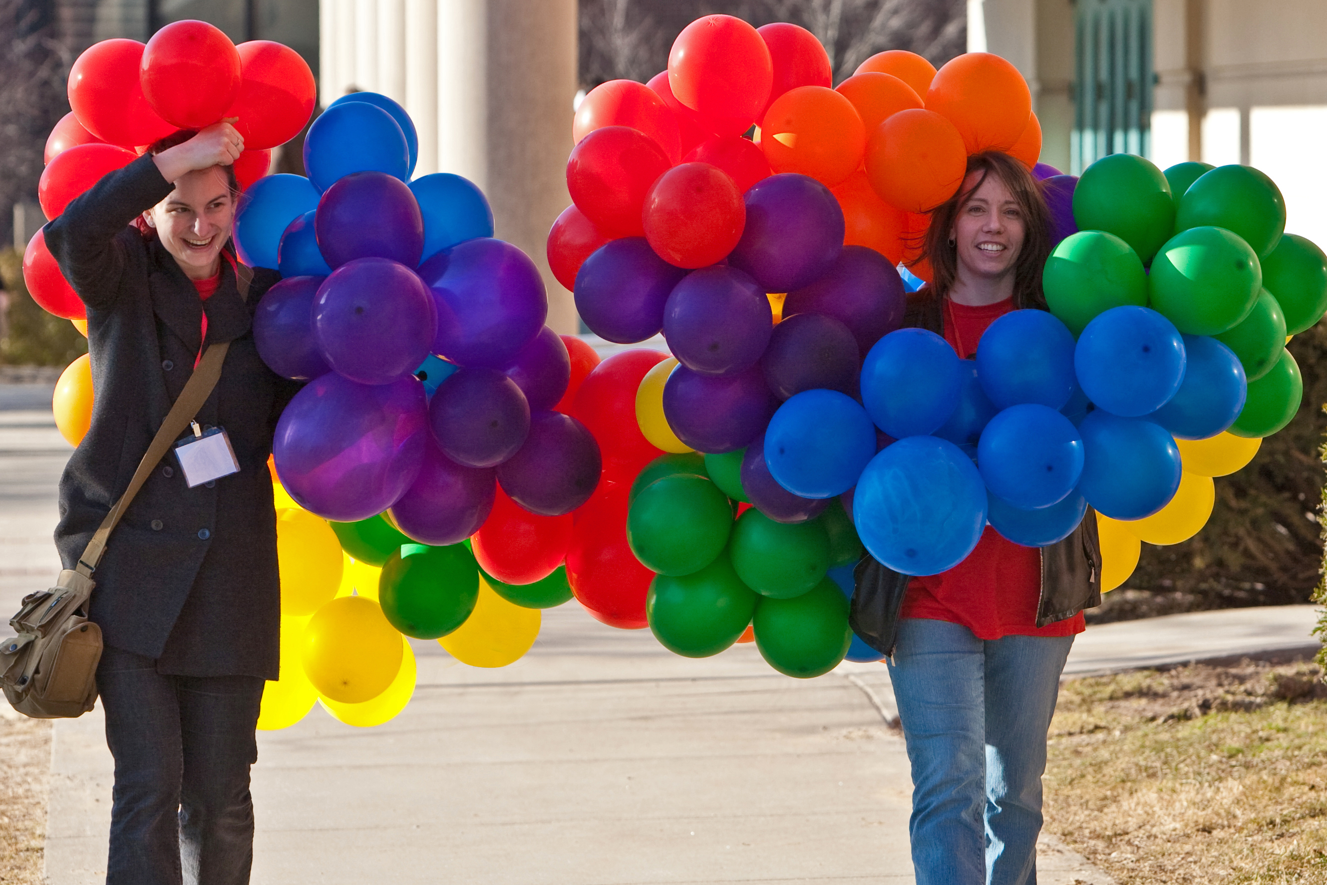 Two people walking with colorful balloons