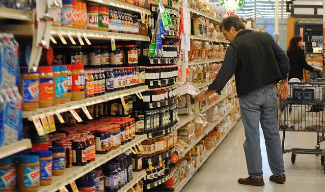 Man in grocery aisle with peanut butter and jam, looking at bread