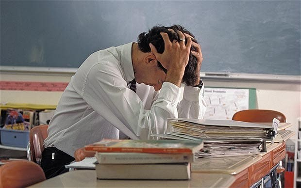 White male teacher at desk with head in hands