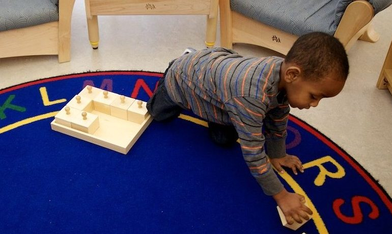 African American preschool aged boy playing with blocks on blue rug