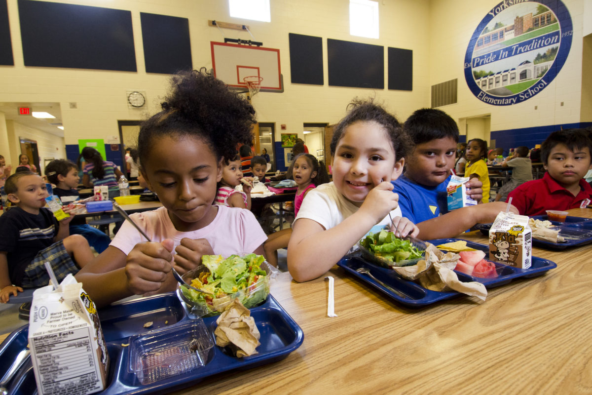 Racially/ethnically diverse children eating at table in cafeteria