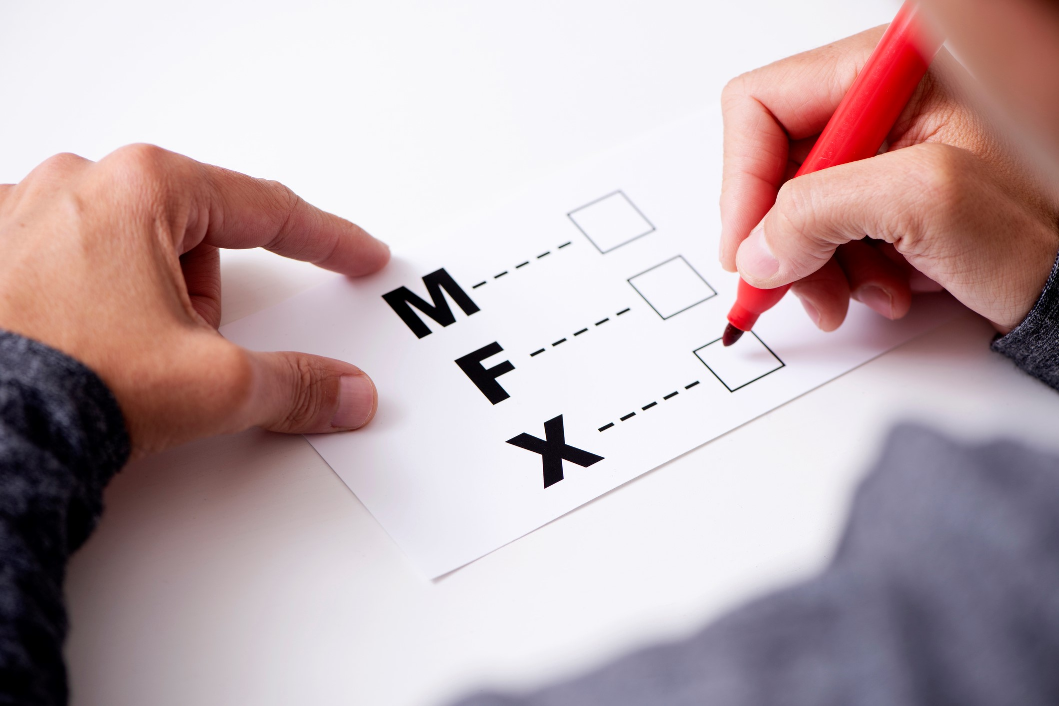 closeup of a young caucasian person about to mark on the X in a form with the letters M for male, F for female and X for the third gender