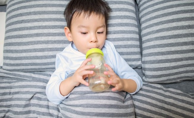 toddler drinking from bottle on bed