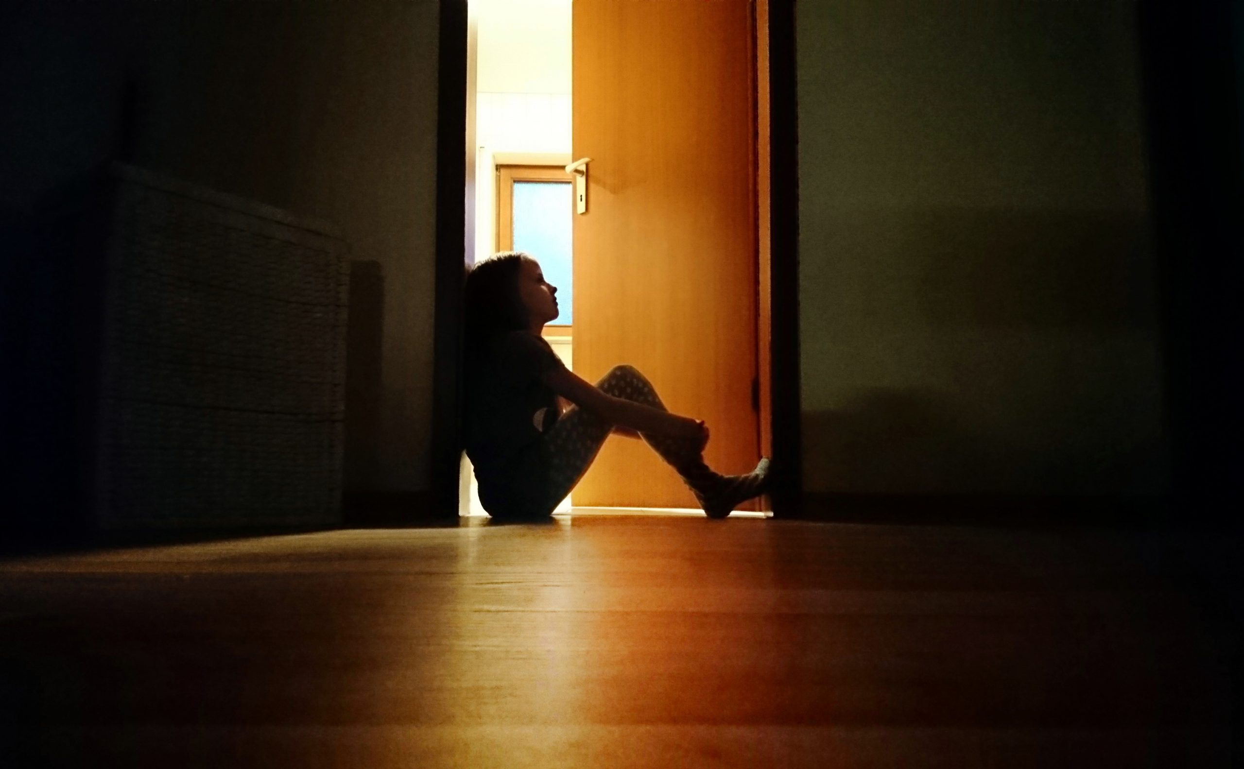 Backlit child sitting in a dark doorway in contemplation