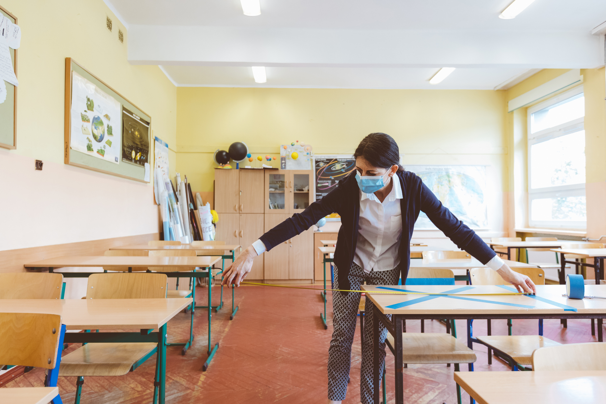 Female teacher measuring and marking places in the classroom that are to be empty after students return to school after the coronovirus pandemic. Covid-19