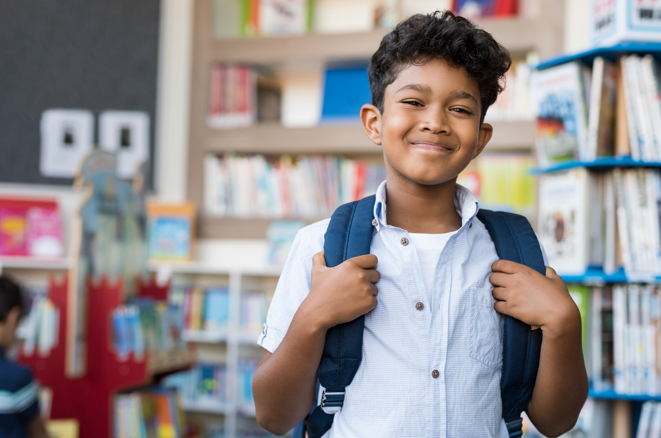 Portrait of smiling Latino boy looking at camera. Young elementary schoolboy carrying backpack and standing in library at school. Cheerful middle eastern child standing with library background.
