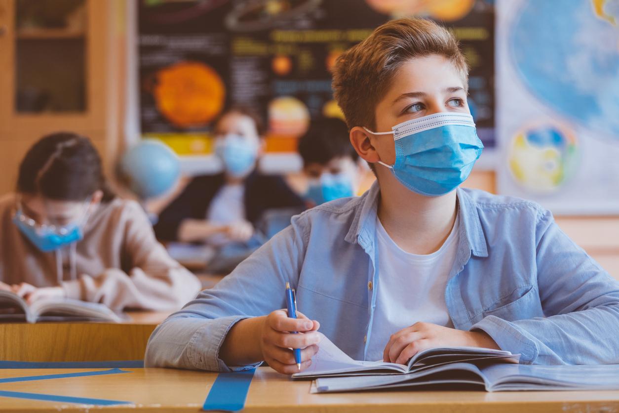 High school students at school, wearing N95 Face masks. Teenage white boy sitting at the school desk, looking away and thinking.