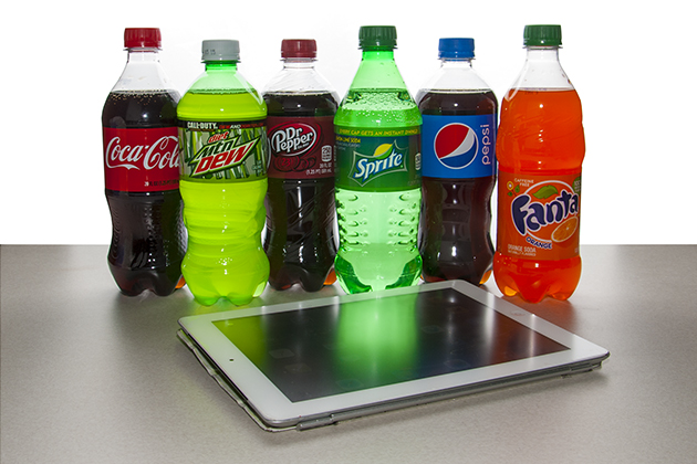 Assorted soda bottles behind tablet