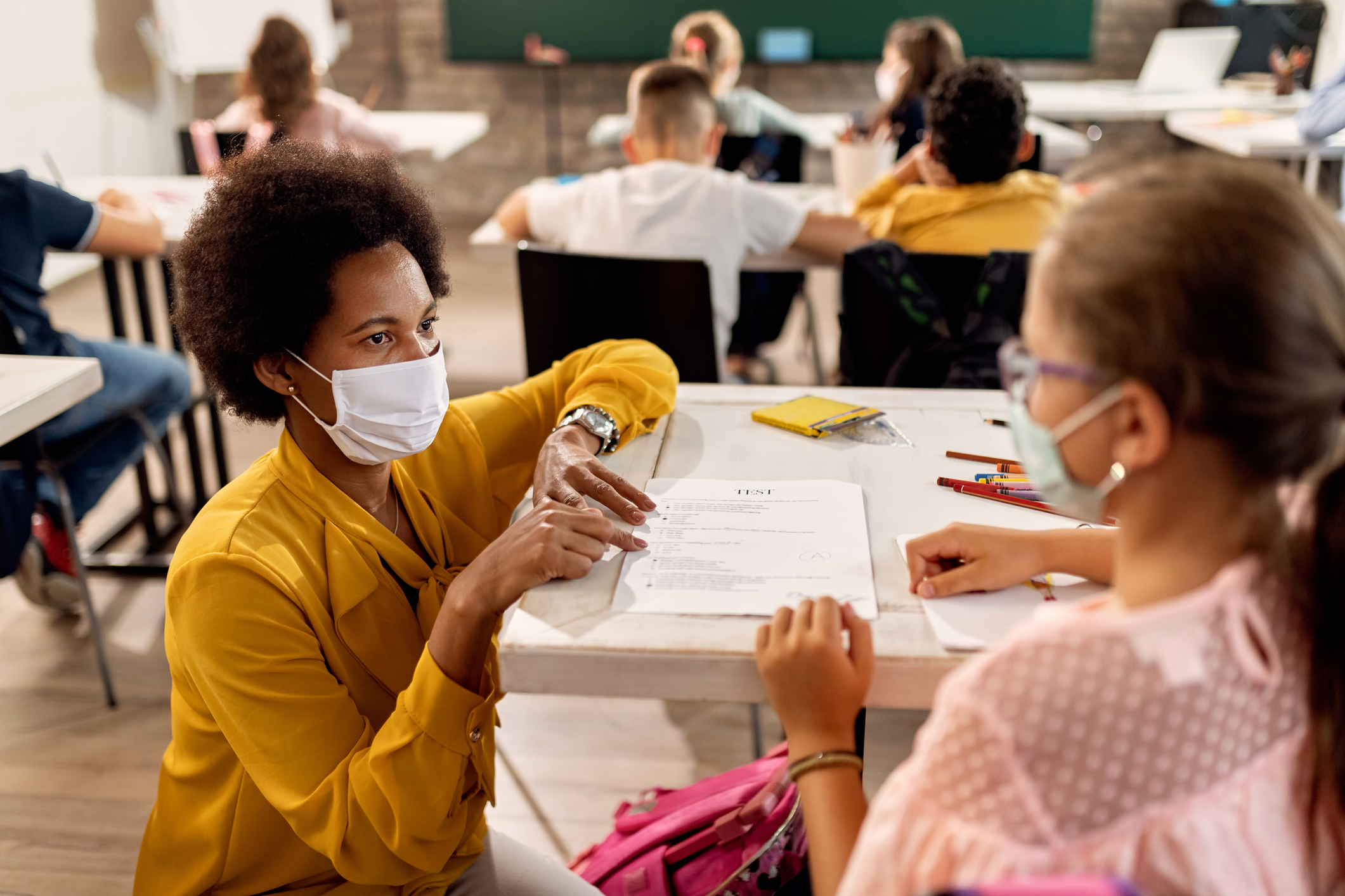 Black teacher with a face mask explaining exam results to elementary student in the classroom