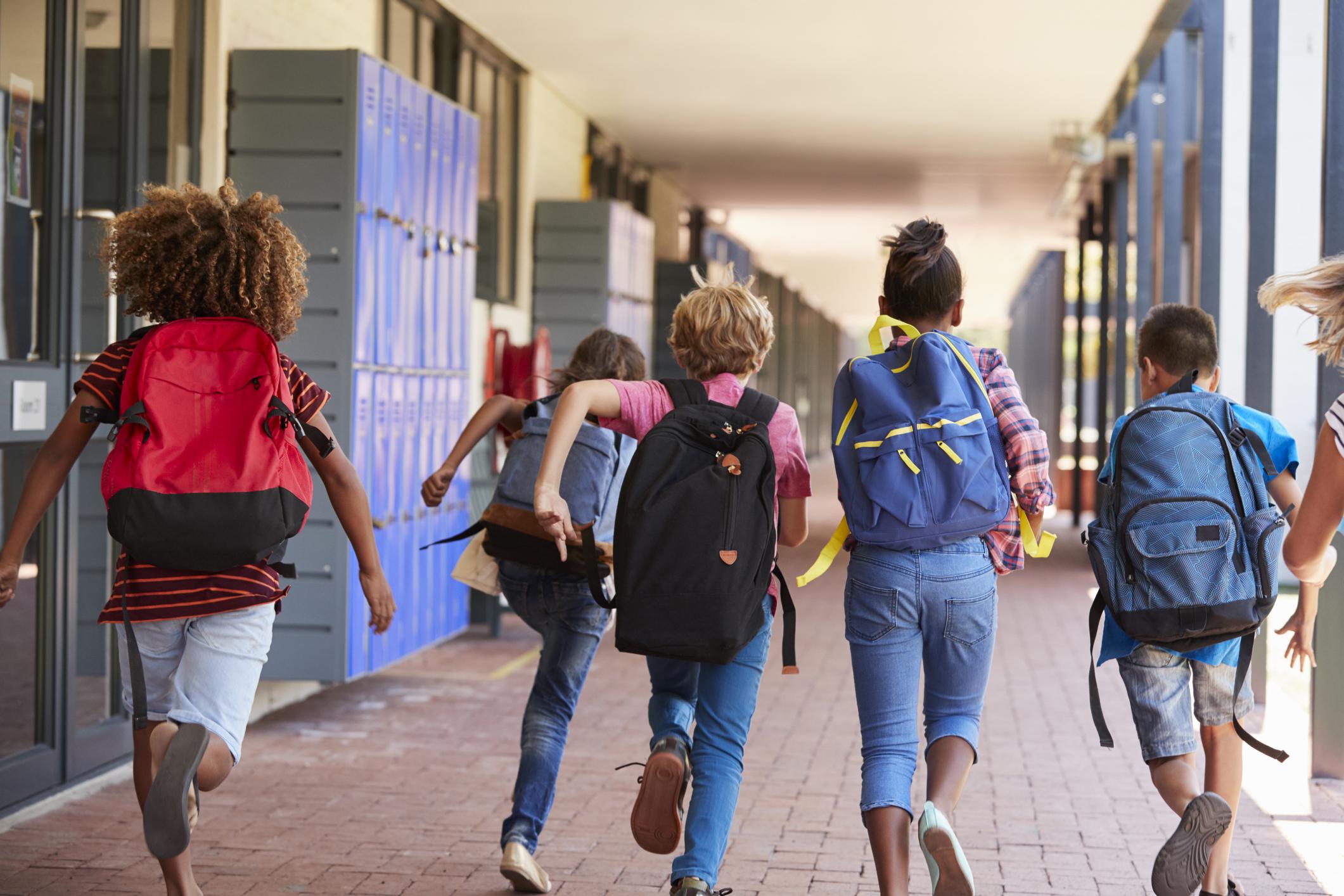 School kids running in elementary school hallway, back view