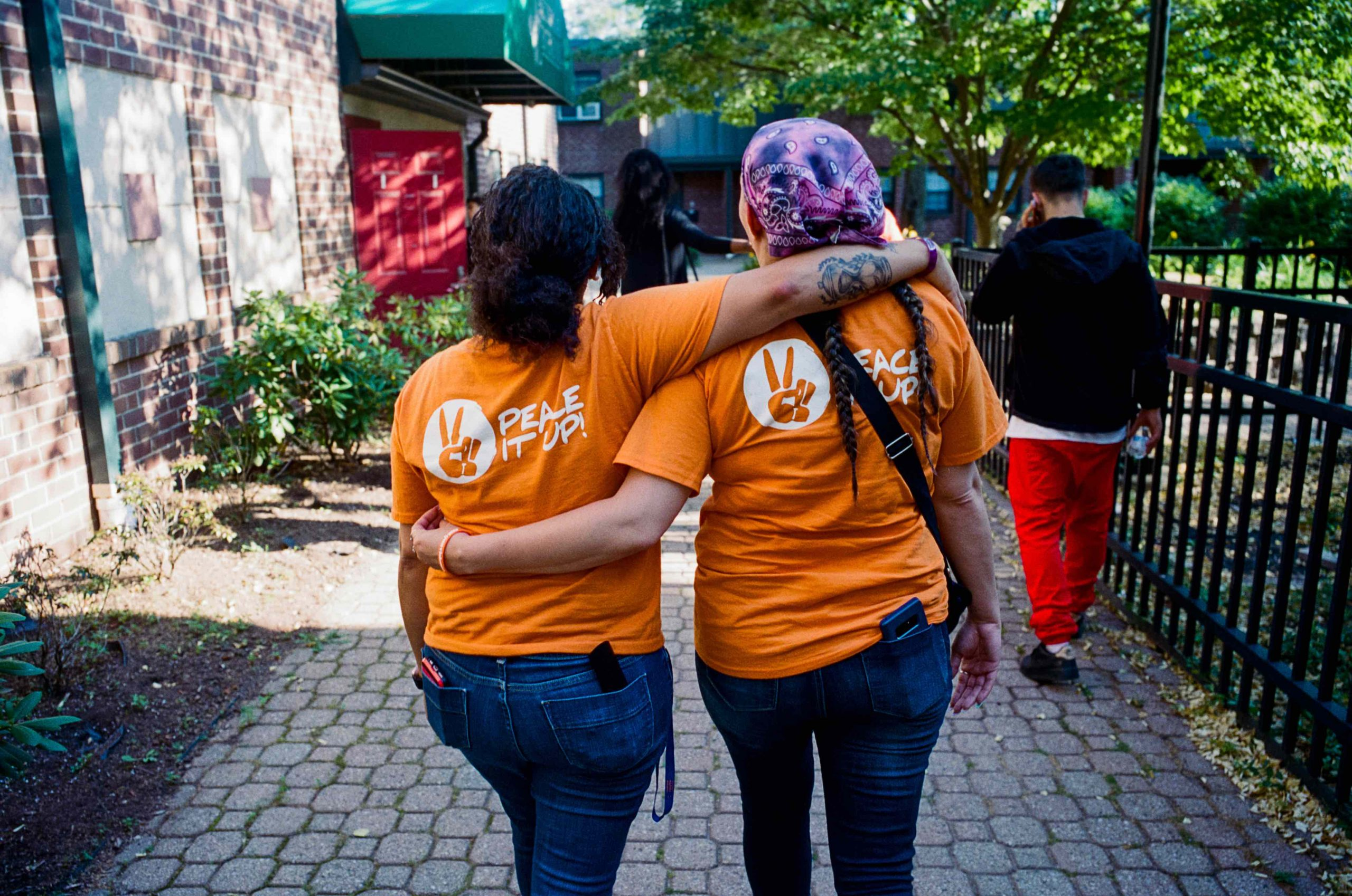 two women walking away from camera wearing jeans and orange t-shirts with Peace it up written on the back