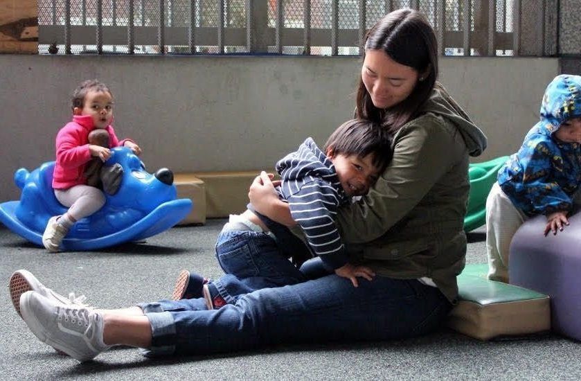 young mother with long dark hair sits on the floor with legs stretched out and little toddler boy snuggles on her lap