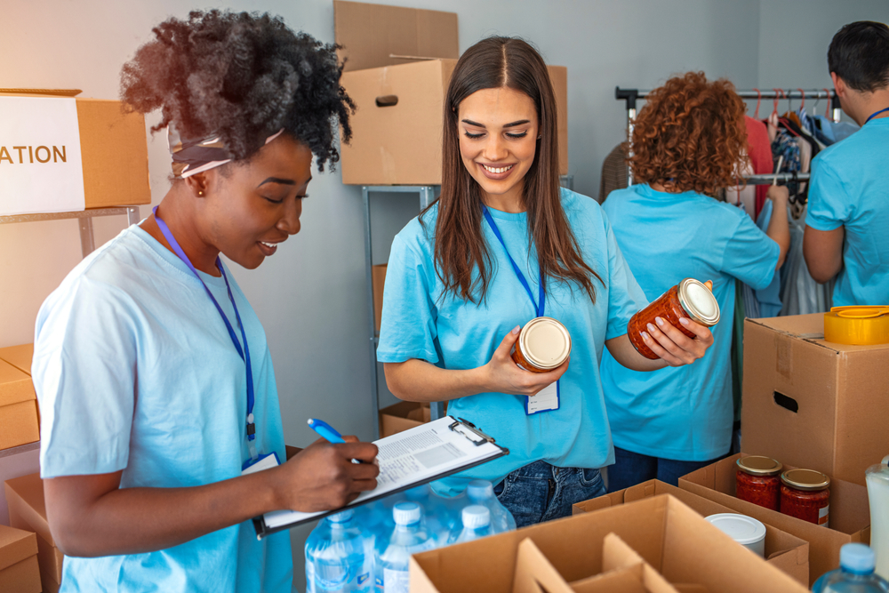 Two women, one Black and one White, volunteering in a food pantry pack boxes for distribution to hungry people. The Black woman holds a clipboard and is smiling; the White eoman holds two jars of tomato sauce.