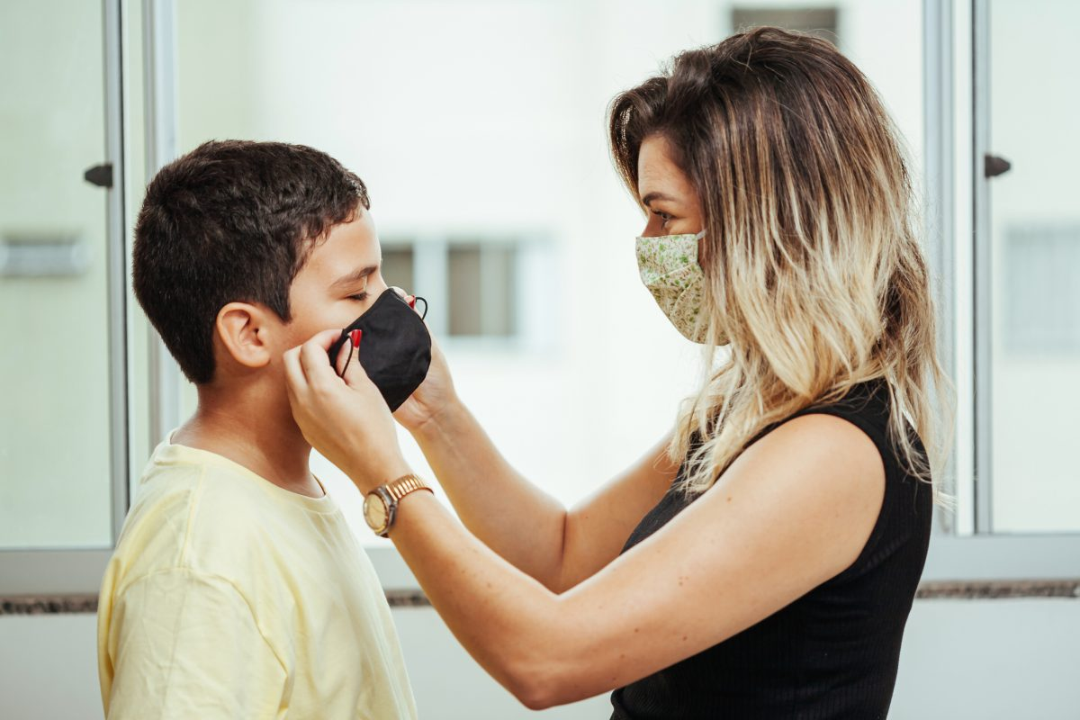 Mother wearing white and green cloth face mask faces son while putting on black coth fask mask on this face.
