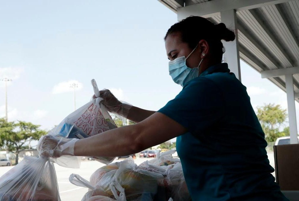Woman with face mask prepares plastic bags filled with food for distribution