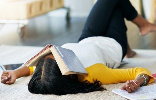 female college student lies back on bed surrounded by notebooks with open book resting on her face