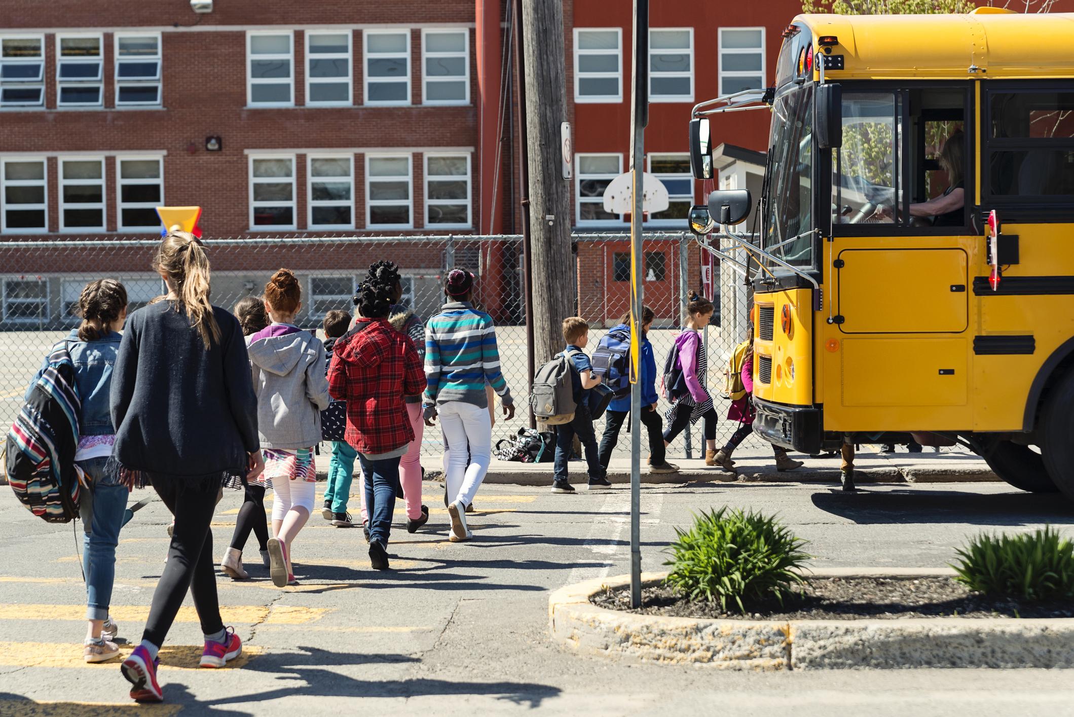 Kids in line crossing street to get on school bus in front of school building.