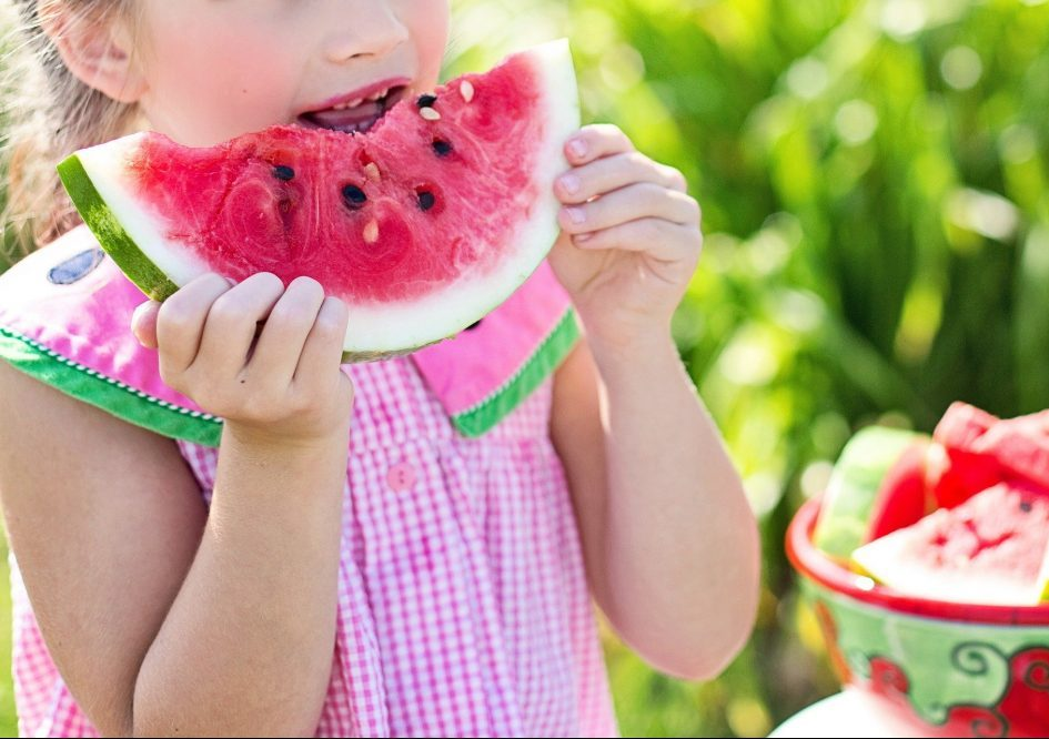 white girl in pink and white checked dress eating watermelon
