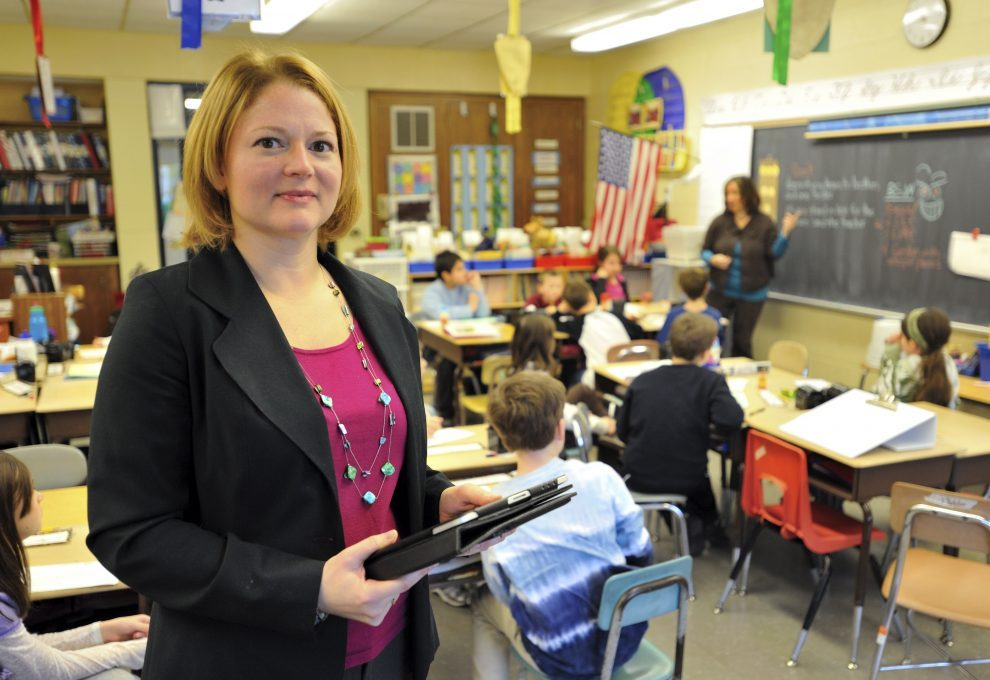 Sandra Chafouleas stands in front of a classroom of kids holding a binder and iPad. She is a white eoman with blonde hair wearing a raspberrry shirt with black blazer.