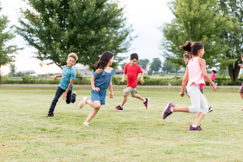 A diverse group of elementary school students play tag outside at recess. They are running around the grass outside of the school.