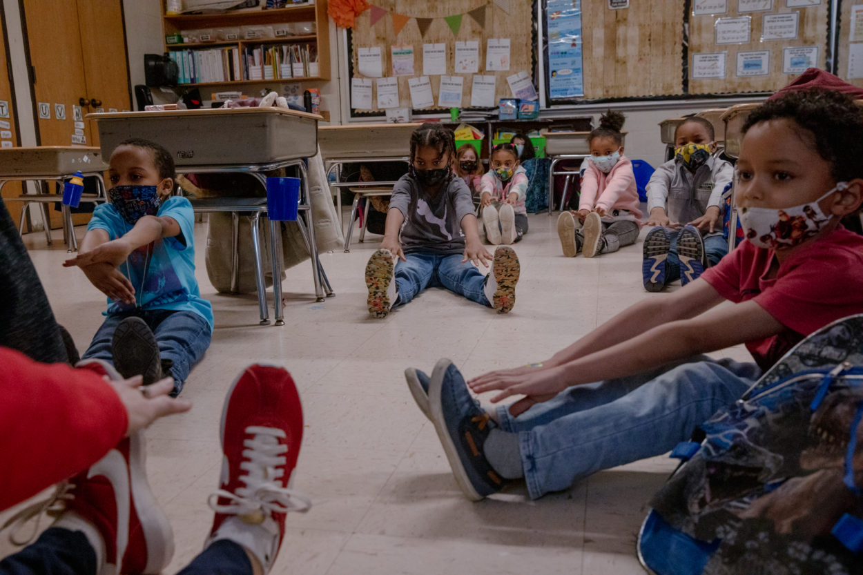 Group of young, diverse kids in school sit on the floor with legs stretched out and touching their toes. They are wearing masks