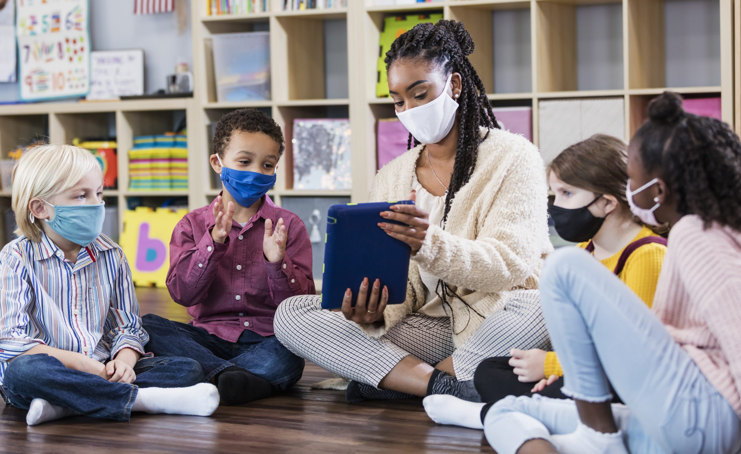 Black woman teacher sits cross-legged with diverse children in school classroom. All of them are wearing masks. The teacher shows one student something on a tablet.