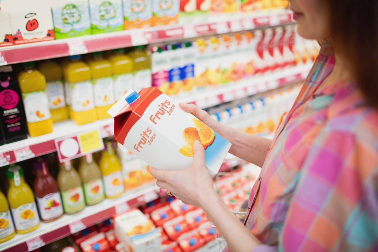 White woman with long brown hair wearing colorful plaid shirt stands in grocery store aisle holding carton reading