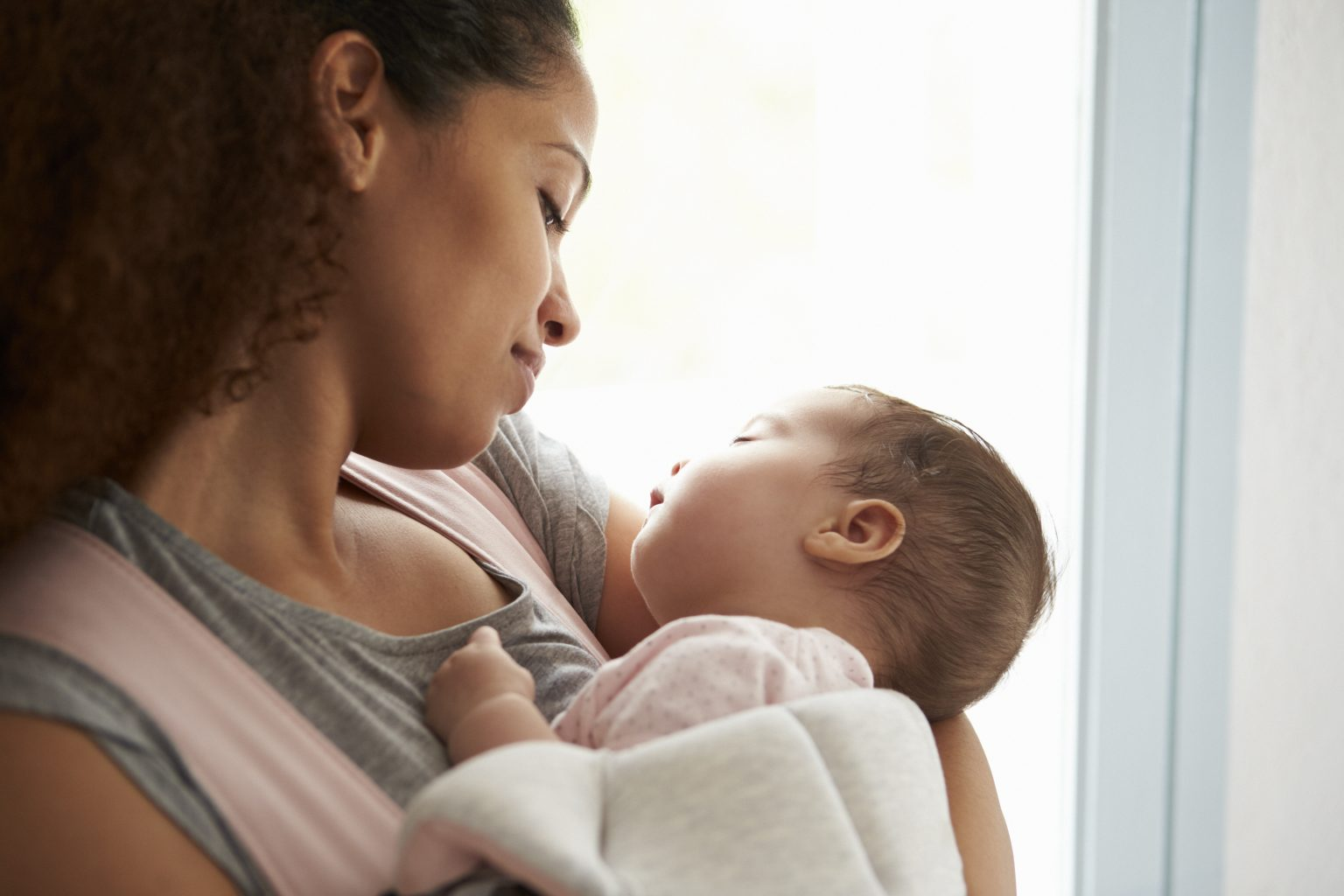 Black mother looking down at infant in her arms with smile