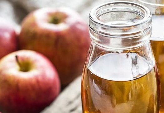 a glass jar filled with apple juice in the foreground with apples and other jars in the background