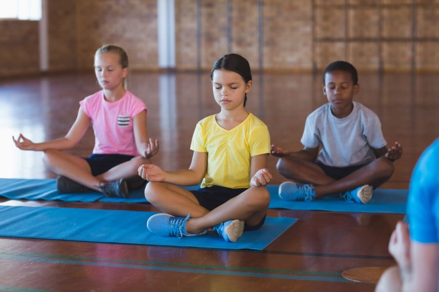 Two girls and a boy sit cross-legged, with eyes closed and hands palm up on knees, on yoga mats in a school gym. The girl in the foreground has brown hair and is wearing a yellow shirt. The girl on the left back is white with blonde hair wearing a pink shirt. The boy on the back right is Black with short hair, wearing a grey shirt.