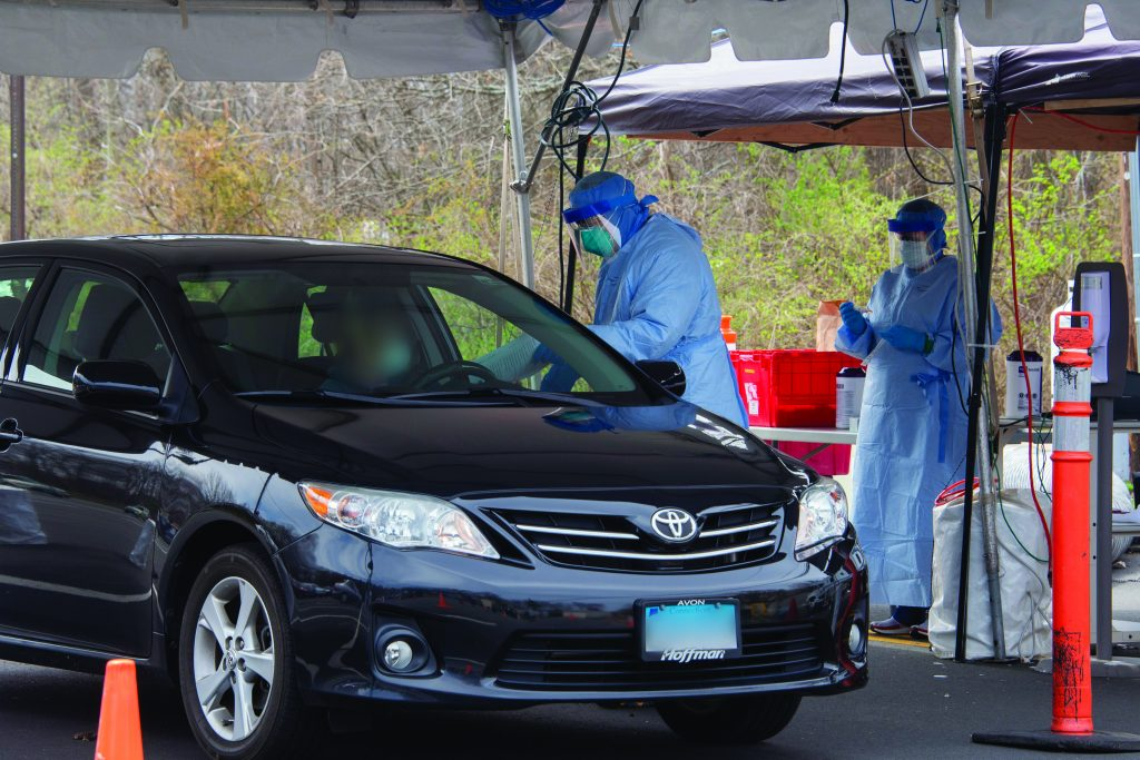 A black Toyota sedan pulls up to two health workers in PPE under a tent administering drive through COVID-testing