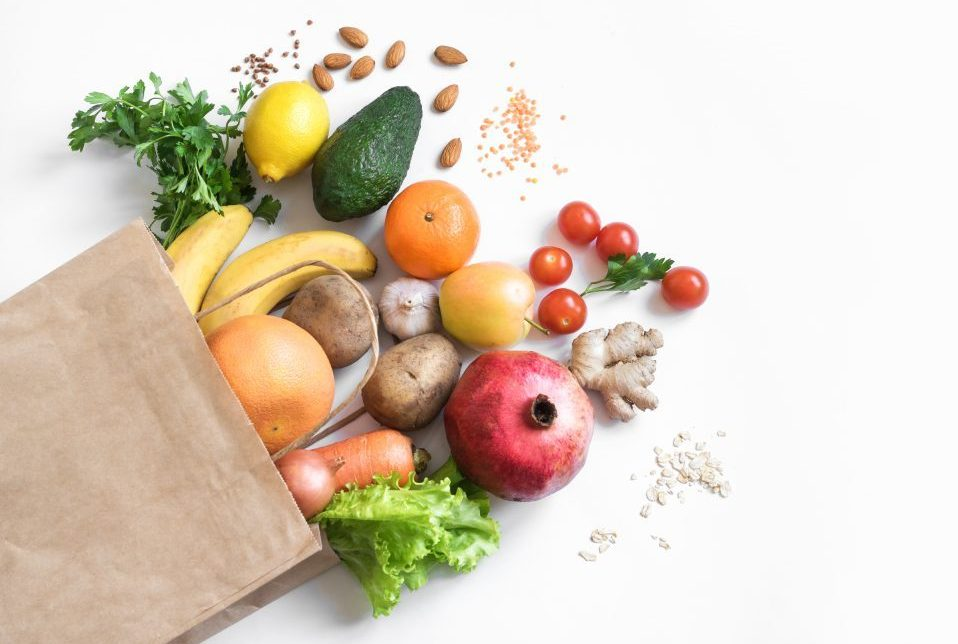 brown paper grocery bag lying on its side with fruits and vegetables spilling out