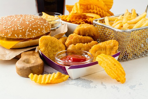 Cheeseburger, chicken nuggets with kethchup, basket of fries and potato chips on a table