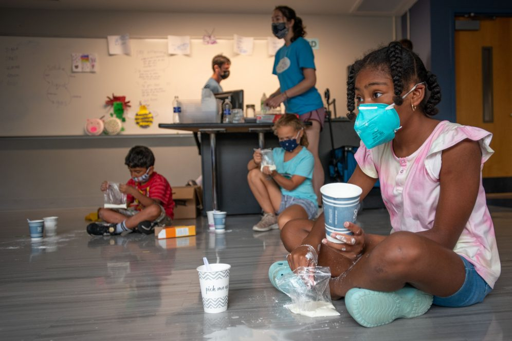 Kids making oobleck at UConn BRAIN Camp; Black girl sits in foreground on floor adding baking soda to a cup