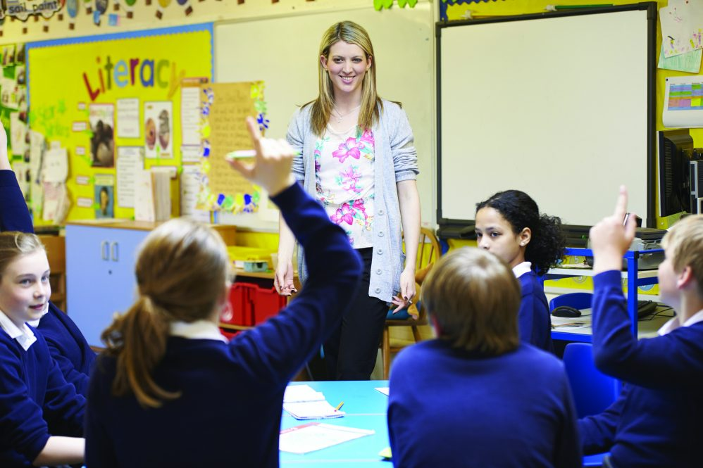 white blinde teacher in classroom with girls in blue sweater school uniforms