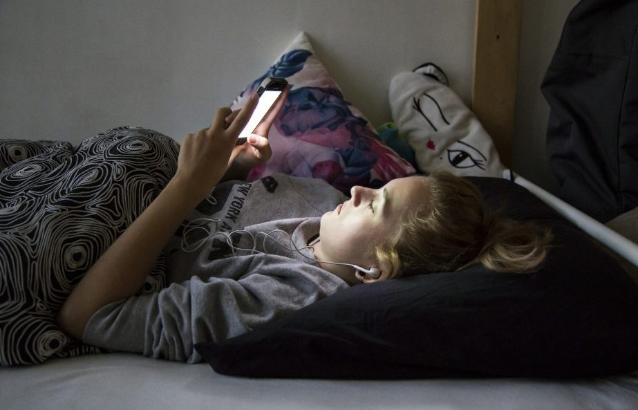 Teenager is lying on bed, looking mesmerized at her phone in dar