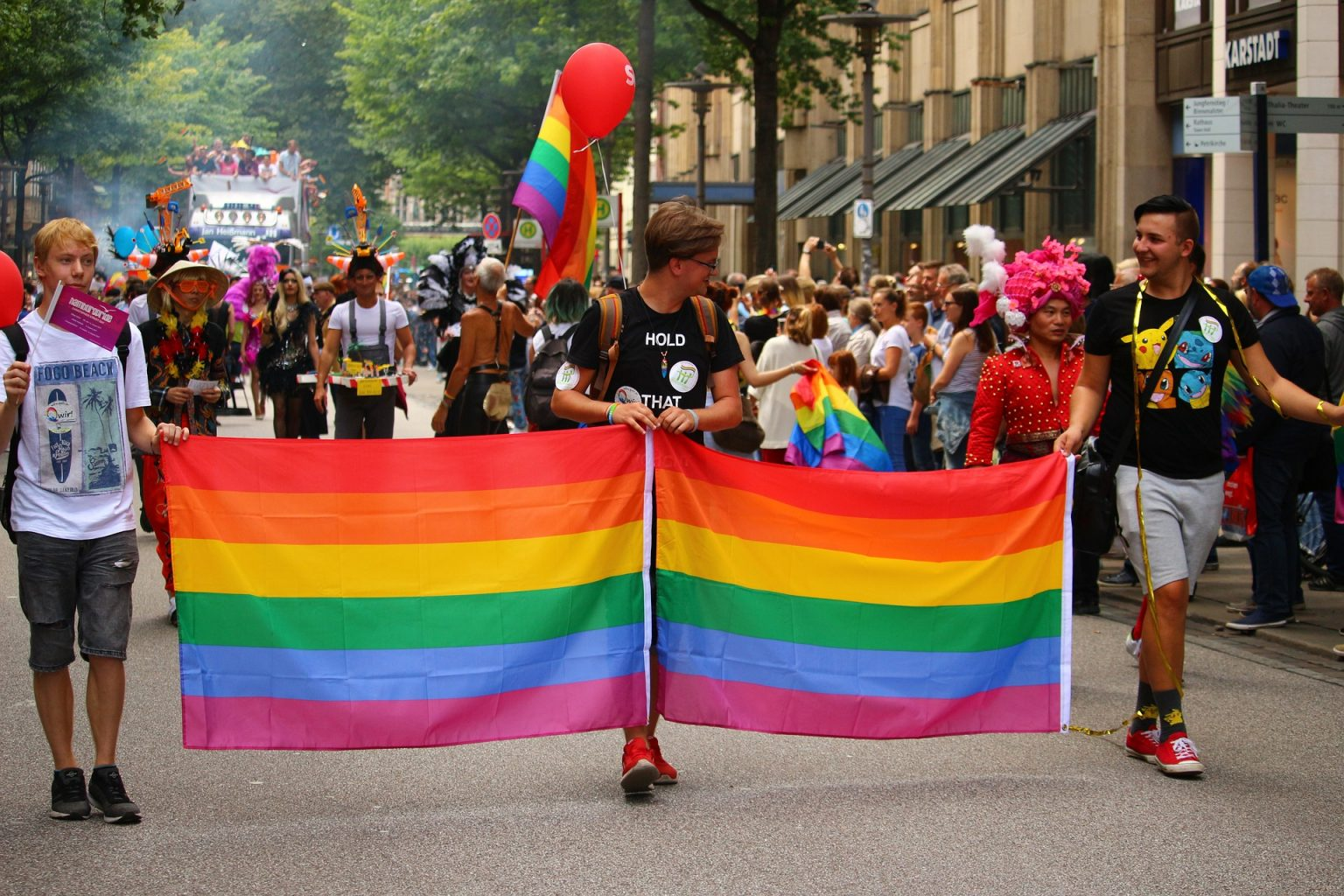 Three young people hold a pride flag in an LGBTQ pride march
