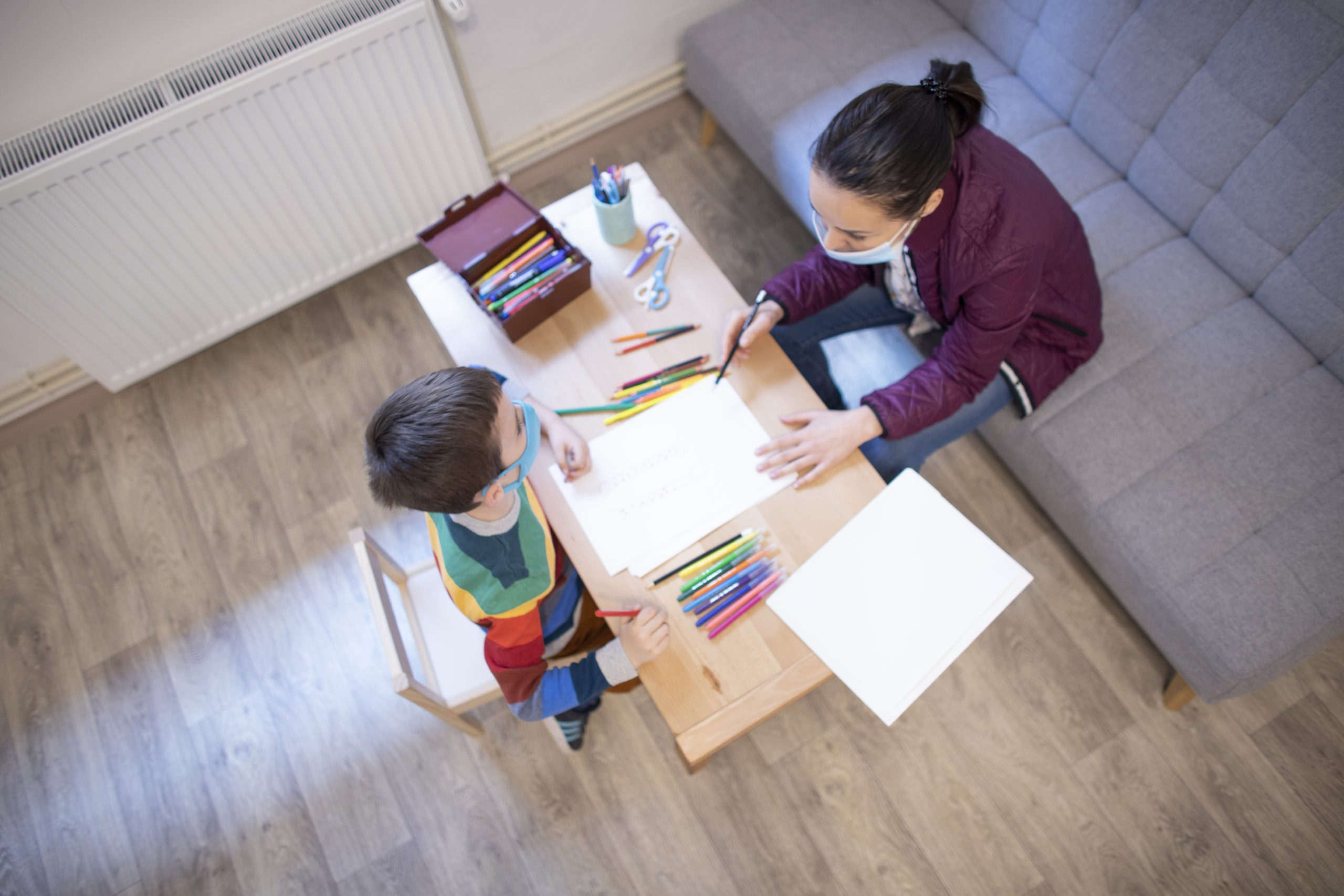 Bird's eye view of six year old white boy wearing mask working with a white, female psychologist wearing a mask at the psychotherapy session..