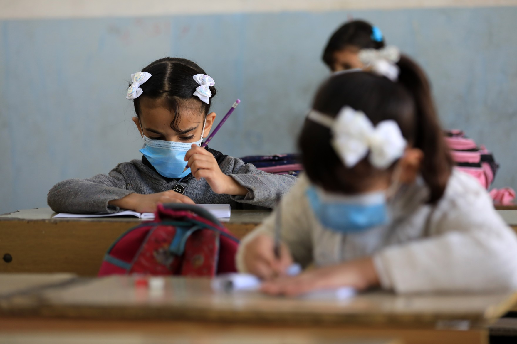 girls sit at desks in classroom with masks