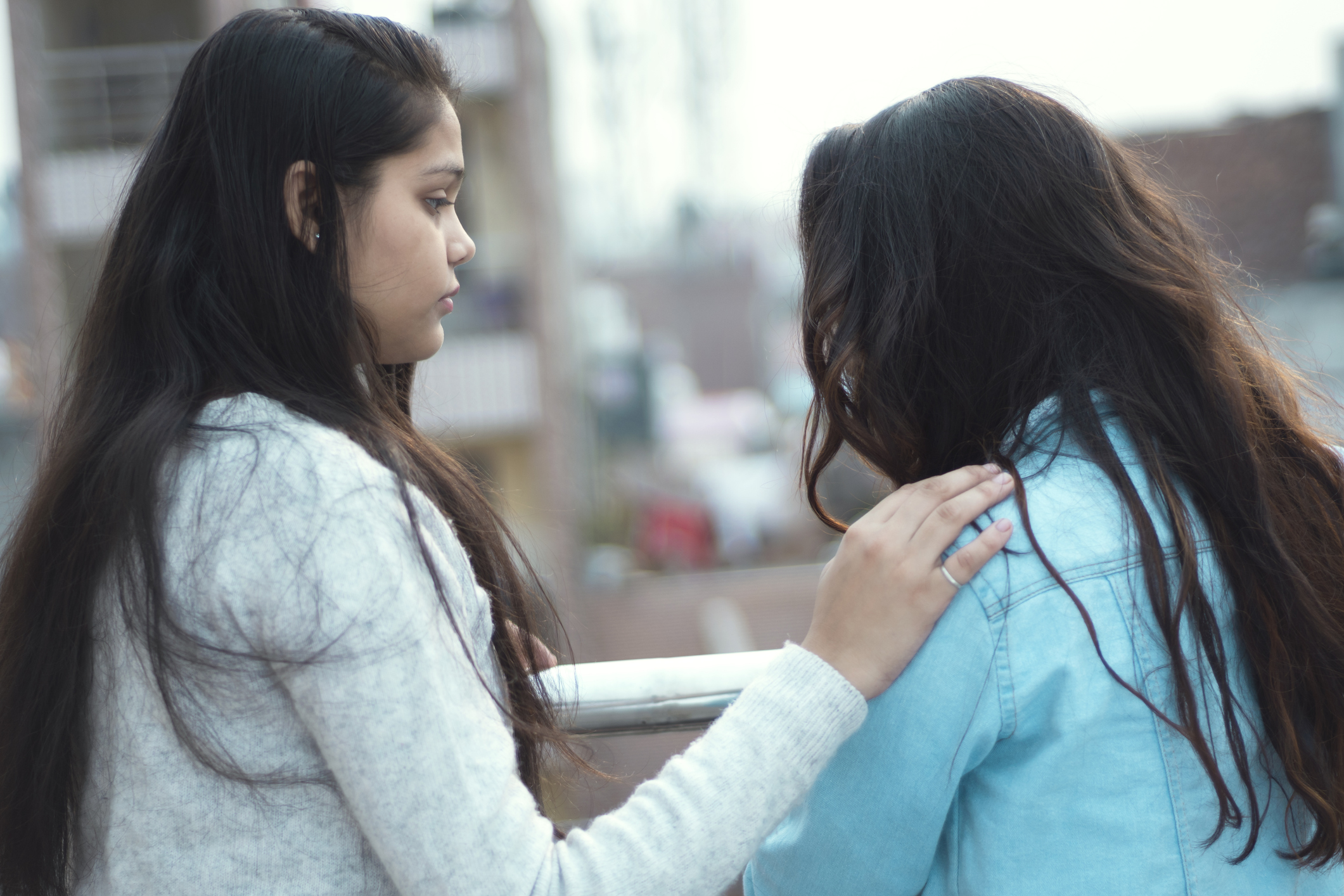 Young woman of color consoling to a depressed friend. outdoor shoot, girls standing in balcony.